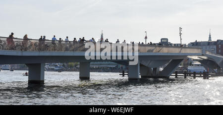 Copenhagen, Denmark - 25 June 2019: people riding bikes on the bridge in the center of Copenhagen, Denmark - Stock Photo