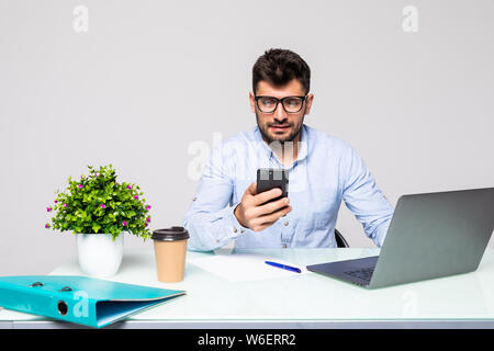 Young businessman in shirt sits in office at table and uses smartphone and drinks coffee on desk with laptop. - Stock Photo