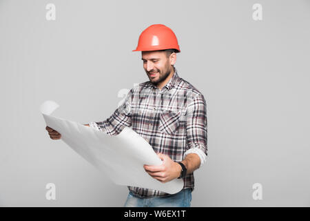 Male Caucasian construction engineer looking at blueprints while wearing formal suit and helmet, isolated on white background - Stock Photo