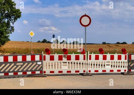 Blocked road at a construction site on a northern german road on a sunny day - Stock Photo
