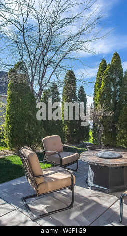 Vertical Upholstered metal chairs and round table at the patio of a home under blue sky - Stock Photo