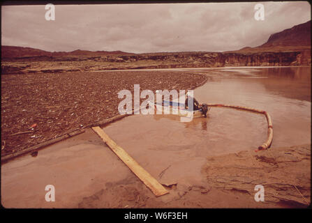 AT SITE OF OIL-SPILL CLEAN-UP OPERATIONS IN A REMOTE AREA OF THE SAN JUAN RIVER. BOAT PUSHES OIL-LADEN DEBRIS TO A POINT WHERE A DRAGLINE SHOVEL CAN REACH IT. SPILL ORIGINATED NEAR SHIPROCK, NEW MEXICO. OIL FLOWED 200 MILES DOWNSTREAM UNTIL TEMPORARILY CONTAINED BY THE LOG BOOM PICTURED HERE. JUST BEYOND BOOM SITE IS THE NORTHEASTERN TIP OF LAKE POWELL - Stock Photo