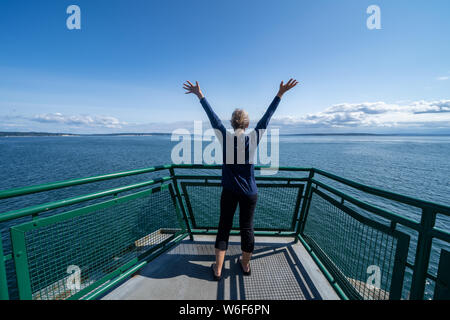 Woman passenger on the Port Townsend Ferry in Washington State stands with her arms up and back to the camera as the boat sails across Puget Sound - Stock Photo