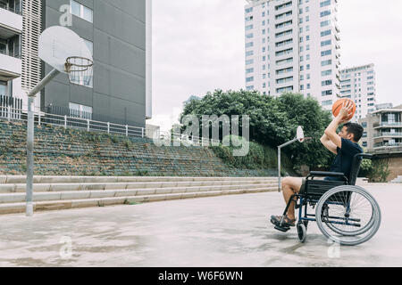 handicapped man in wheelchair playing basketball alone, concept of adaptive sports and physical activity, rehabilitation for people with physical disa - Stock Photo