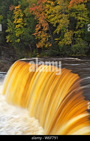 The Tahquemenon River with its amber colored water from naturally occurring tannin found cascades over Tahqemenon Falls in Michigan's Upper Peninsula. - Stock Photo