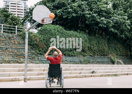 handicapped man playing basketball alone in the city, concept of adaptive sports and physical activity, rehabilitation for people with physical disabi - Stock Photo