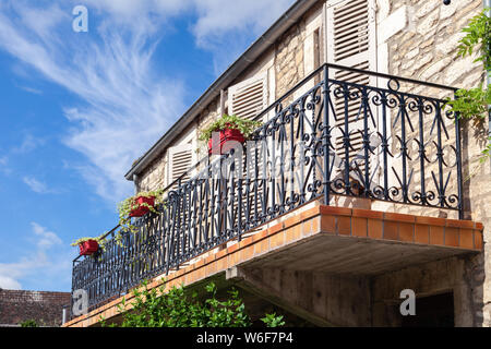 Cozy vintage French balcony with black metal railings, flowers in pot, open shutters on windows against blue sky, clouds. Bottom view. Concept tourism - Stock Photo