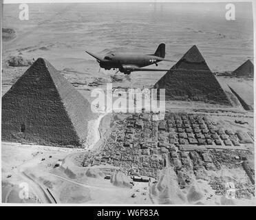 An Air Transport Command plane flies over the pyramids in Egypt. Loaded with urgent war supplies and materials, this plane is one of a fleet flying shipments from the U.S. across the Atlantic and the continent of Africa to strategic battle zones.; General notes:  Use War and Conflict Number 1015 when ordering a reproduction or requesting information about this image. - Stock Photo