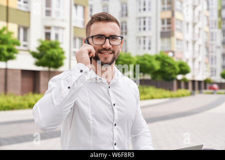 Close up of young, stylish, bearded man talking by phone on background of modern city with multistory houses. Positive businessman in glasses wearing in white shirt looking at camera. - Stock Photo