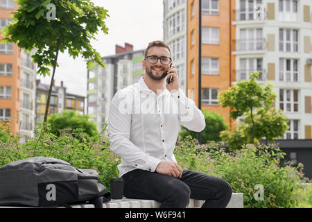 Young freelancer sitting on bench, talking by phone, looking at camera. Handsome man in glasses wearing in white stylish shirt. It worker smiling, posing on background of modern city. - Stock Photo
