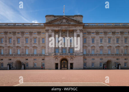 Facade of Buckingham Palace with two members of the Queens Guard in front, London, United Kingdom - Stock Photo