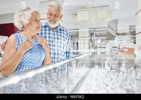 Cheerful bearded senior man in checkered shirt embracing his beautiful wife in blue dress that trying on pearl necklace at jewelry store. Grey haired husband doing pleasant present to beloved woman - Stock Photo