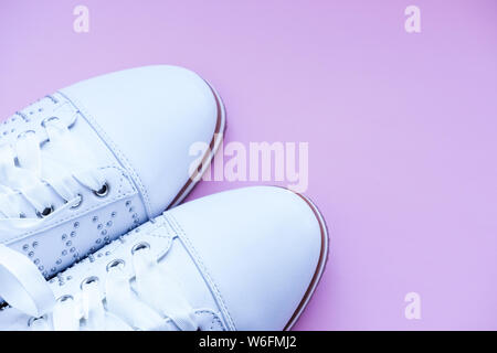 Shoes for young girl, woman fashion. white leather sneakers with laces. Stylish casual shoes. Fall street fashion outfit. White boots isolated on pink - Stock Photo