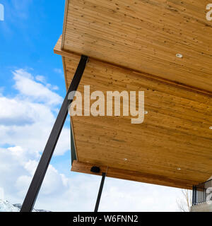 Underside of roof with brown wooden planks and round ceiling lights against sky - Stock Photo
