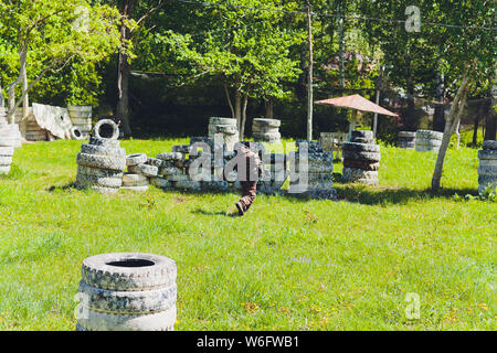 Paintball sport player in protective uniform and mask playing with gun outdoors. - Stock Photo