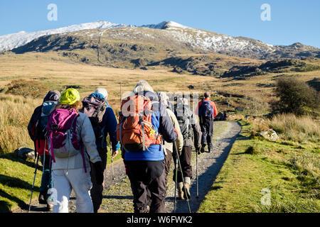 Ramblers group hiking on Rhyd-Ddu path to snow covered Mt Snowdon peak in mountains of Snowdonia National Park. Rhyd-Ddu Beddgelert Gwynedd Wales UK - Stock Photo