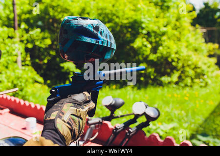 Man in camouflage suit stands against the paintball area with his paintball gun up and looks straight ahead. - Stock Photo