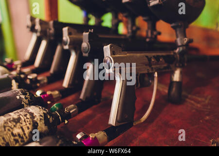 Paintball guns on a wooden table. play paintball. - Stock Photo