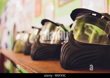 black and green paintball helmet. Mask, a helmet for a game in a paintball. - Stock Photo