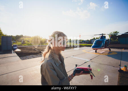 Beautiful smiling young red head woman using drone. enthusiastic pilot girl driving Flying drone with remote controller. - Stock Photo