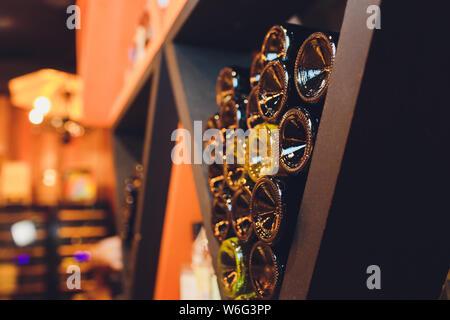 Resting wine bottles stacked on wooden racks in cellar. - Stock Photo
