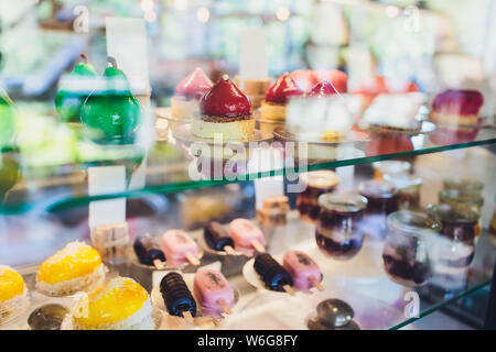 Showcase with sweets chocolate milk Strawberry fruit cakes for sale in cake shop. Different types Cake tray in showcase. Glass display at store bakery - Stock Photo