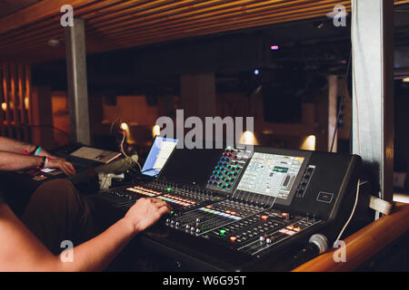 studio working with sound and light mixer console,hands of sound engineer working on recording studio mixer adjusting the volume of a sound mixer - Stock Photo