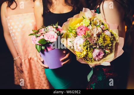 Two Small Beautiful bouquets of mixed flowers in woman hand. Floral shop concept . Beautiful fresh cut bouquet. Flowers delivery. - Stock Photo