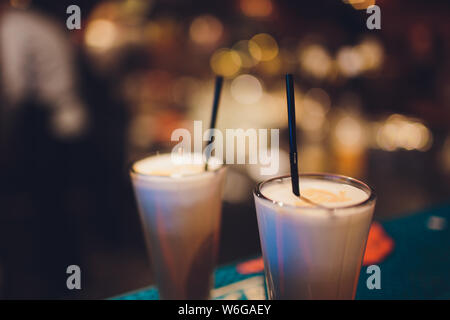 Two delicious thick icecream milkshakes garnished with chocolate and mint and served in tall chilled glasses on a small old wooden tray. - Stock Photo