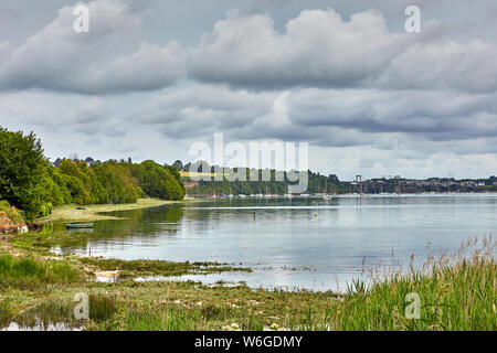 Image of the Rance Estuary in France with Plouer Sur Rance Marina and Pont Saint Hubert bridge  in the back ground with cloundy sky and yachts on moor - Stock Photo