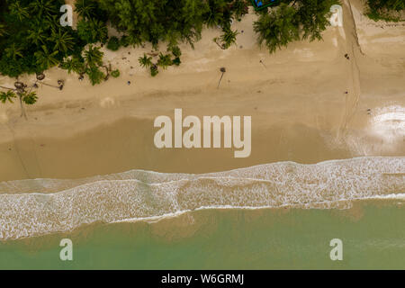 Aerial view of waves breaking on an empty, sandy tropical beach