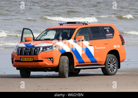 Dutch lifeguard Toyota Land Cruiser with active blue emergency lighting on the beach - Stock Photo