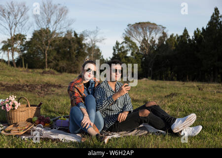 man and woman sitting with glasses taking selfies under the sun - Stock Photo