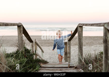 Young child reaching for handrail on beach path Stock Photo