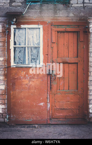 Facade of an old building with red door on lock and small white window with curtain. - Stock Photo