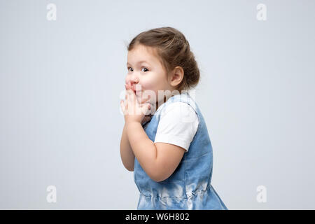Surprised little girl covered mouth with her hands waiting for gift - Stock Photo
