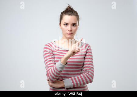 Young woman looks stressed and pointing up with finger saying no - Stock Photo