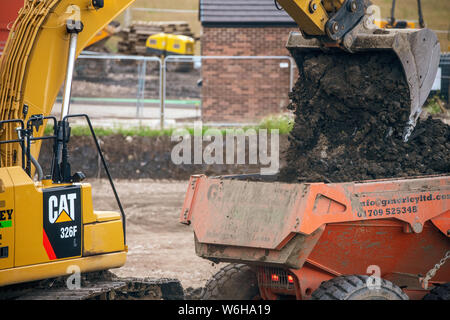 A digger and dump truck move dirt to make room for the foundations - Stock Photo