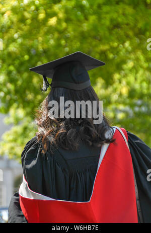 CARDIFF, WALES - JULY 2019: Student with long hair walking in Cardiff city centre after a graduation ceremony - Stock Photo