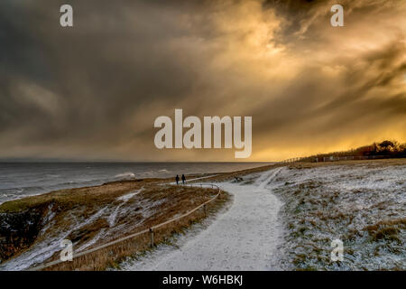 Two figures walking on the snowy path along the coast at dusk; South Shields, Tyne and Wear, England - Stock Photo
