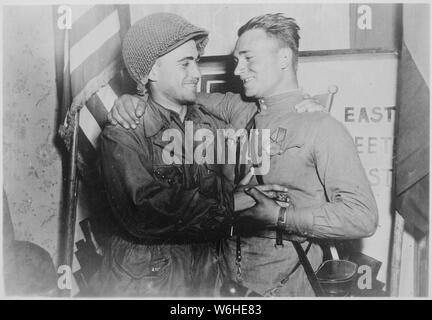 Happy 2nd Lieutenant William Robertson and Lt. Alexander Sylvashko, Russian Army, shown in front of sign [East Meets West] symbolizing the historic meeting of the Russian and American Armies, near Torgau, Germany.; General notes:  Use War and Conflict Number 1096 when ordering a reproduction or requesting information about this image. - Stock Photo