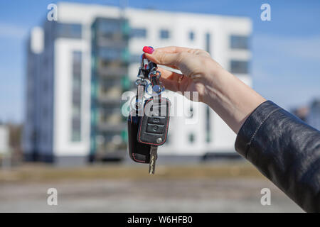 Car keys in a girl's hand on a blurred background of a new house - Stock Photo