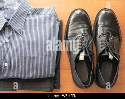 everyday set of mans wear clothes for white collar worker - pants, formal shirt and pair of glossy shoes - Stock Photo
