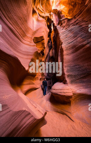 Man standing in a Slot Canyon known as Canyon X, near Page; Arizona, United States of America