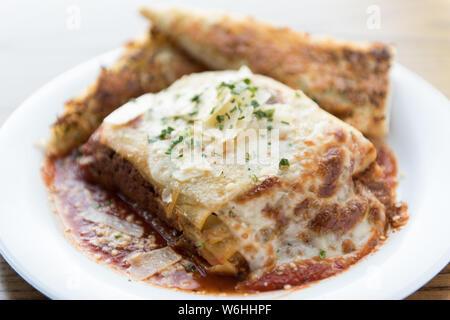 lasagna and garlic bread sit on a white plate - Stock Photo