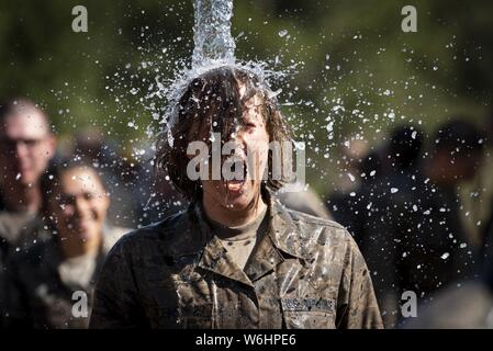 U.S. AIR FORCE ACADEMY, Colo, July 25, 2019. -- Basic Cadets from the class of 2023 immerse themselves in water after completing the assault course on July 25, 2019. The assault course is part of phase two of basic cadet training which takes place out at Jack's Valley on the U.S. Air Force Academy. (U.S. Air Force photo/Joshua Armstrong). () - Stock Photo