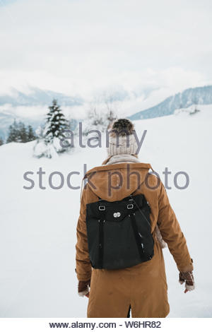 A woman in a tan coat waling on a snowy hillside. - Stock Photo