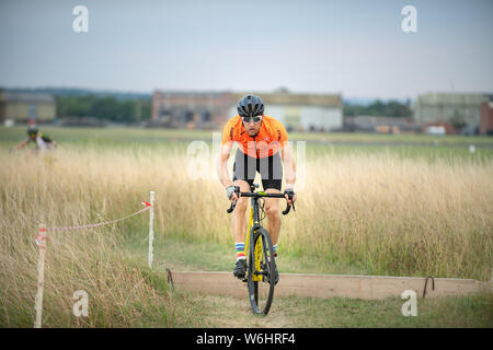 Abingdon, Oxfordshire, UK. 1 August, 2019. Dominic hops over the boards. Take3 Summer CX Series. The cyclocross event at Abingdon Airfield on Thursdays attracts cyclists from ages 6 to 60 something. Cyclocross bike racing in mixed terrain.The weather was warm and partly cloudy.  Credit: Sidney Bruere/Alamy Live News - Stock Photo