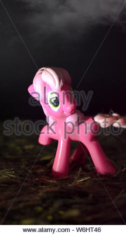 Pink pony doll standing up on a pile of hay. - Stock Photo