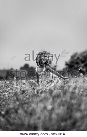 A young girl running through a field of wild flowers. - Stock Photo